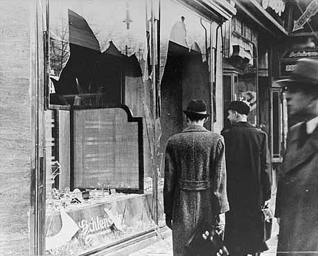 "People walk past broken windows of Jewish shops on the day after the ""Kristallnacht"" pogrom"